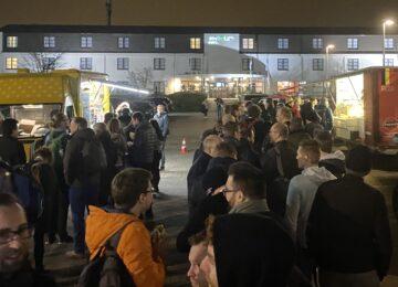 Bezoekers van PHPBenelux 2020 wachten buiten bij de fritekraam en de kraam voor veganistische snacks.